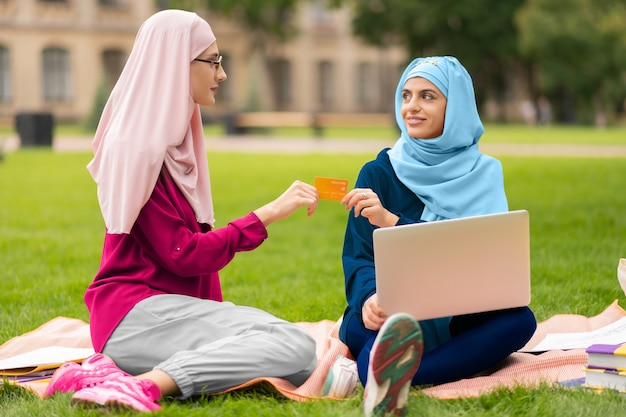 수업 후 쇼핑. 잔디에 앉아 수업 후 온라인 쇼핑 무슬림 학생