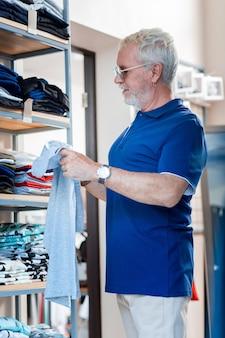 一人で買い物。ファッショナブルなサングラスを通してその価格ラベルを見ながらtシャツを調べる集中した白髪の男性の腰