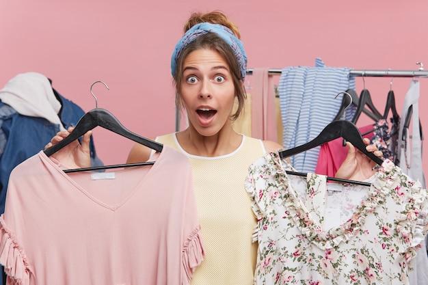 ショッピングと消費者の概念。ワードローブをリフレッシュする時間。幸せな興奮してきれいな女性の口を開けて