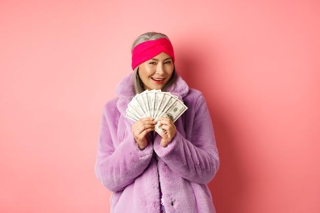 ショッピングとファッションのコンセプト。新しい服を買うことを考えているファッショナブルなアジアの年配の女性、ドルでお金を表示し、貪欲なピンクの背景を笑顔