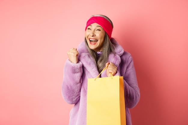 ショッピングとファッションのコンセプト。幸せなアジアの年配の女性が勝ち、紙袋を持って、ピンクの背景の上に立って、陽気な顔でイエスと言って、拳ポンプジェスチャーをします
