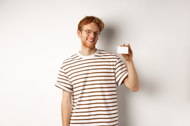 ショッピングと金融の概念。プラスチック製のクレジットカードを示し、白い背景の上に立って、満足そうに見える眼鏡をかけた陽気な赤毛の男子生徒。