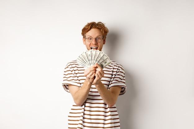 쇼핑 및 금융 개념. 행운의 빨간 머리 남자 우승, 상금을 보여주는 행복 미소, 안경 및 흰색 배경 위에 티셔츠에 서.