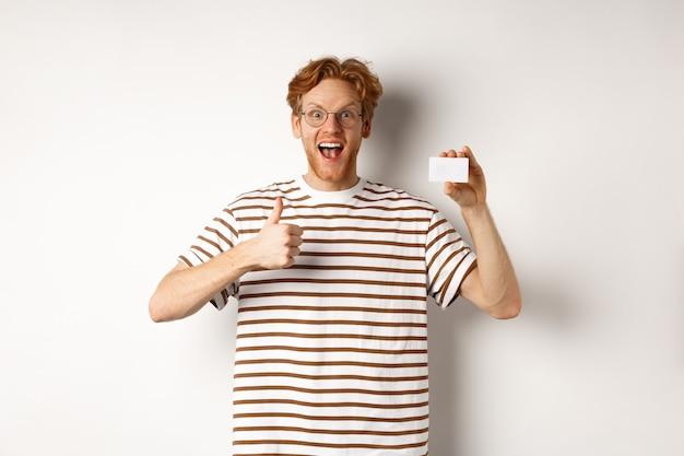 Концепция покупок и финансов. удовлетворенный клиент банка мужского пола показывает палец вверх и пластиковую кредитную карту, счастливую улыбку на камеру.