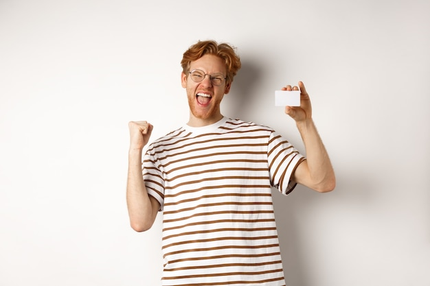 ショッピングと金融の概念。若い男が銀行賞を受賞、プラスチックのクレジットカードを表示し、拳ポンプを作る、喜びと満足から叫ぶ、白い背景