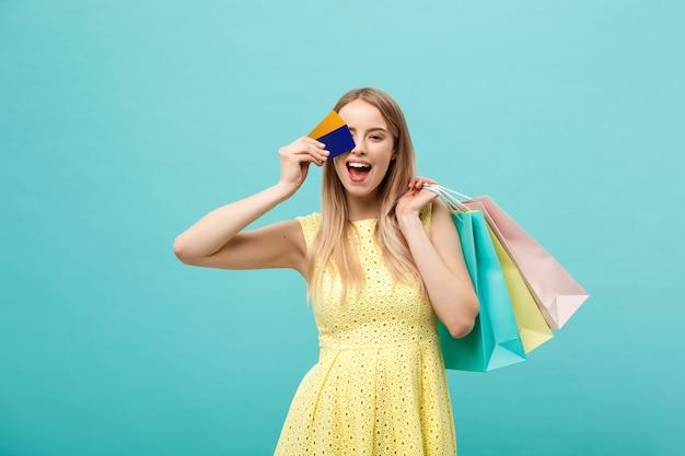 ショッピングとライフスタイルのコンセプト:クレジットカードとカラフルなショッピングバッグを持つ美しい少女。青い背景で隔離。