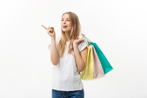 ショッピングとライフスタイルの概念:カラフルな買い物袋を持って指を指す若い陽気な女性。白い背景の上に分離。