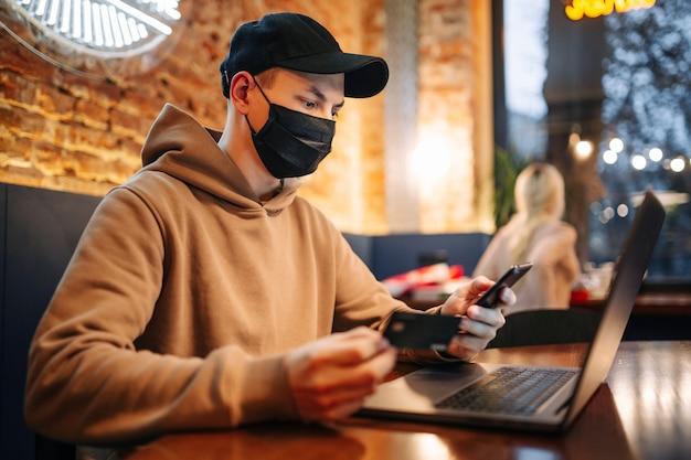 휴대폰, 노트북, 신용 카드를 이용한 쇼핑 및 온라인 결제. 코로나 19 기간 동안 검은 색 의료용 마스크를 쓴 남자가 카페에 앉아 인터넷을 통해 물건을 산다.