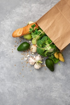 Shopping bag groceries with healthy food top view on a concrete  copyspace