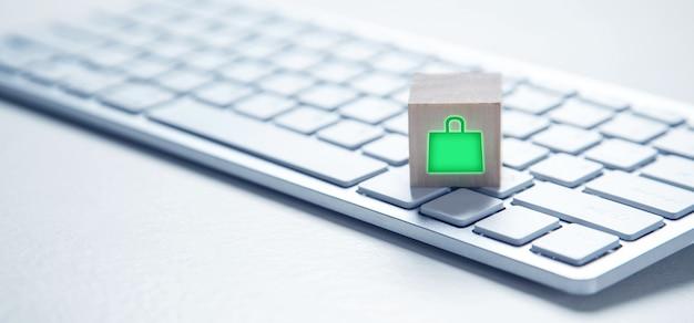 コンピューターのキーボードと木製の立方体の買い物袋のアイコン。