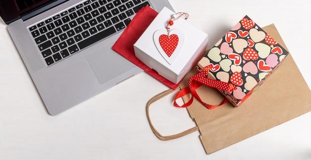 ショッピングバッグ、ラップトップ、白い箱、一杯のコーヒー、ビスケット、白い壁に赤いハートのバレンタインデー、配達のコンセプト。