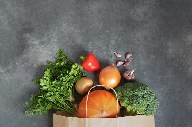 暗いテーブルに新鮮な有機野菜がいっぱい入った買い物袋紙。廃棄物ゼロでは、プラスチックのコンセプトが少なくなります。