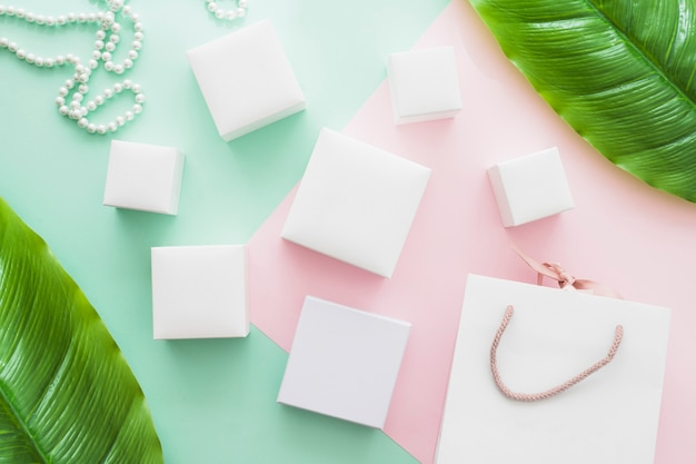 Shopping bag, pearl necklace and different type of white boxes on pastel paper background