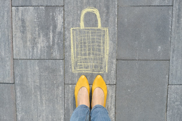 Shopping bag picture written on gray sidewalk in crayons