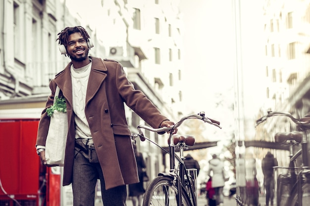 Shopping bag. pleased bearded male keeping smile on his face while listening to music
