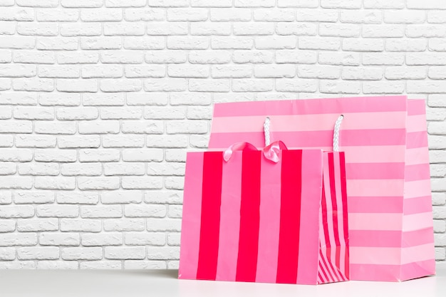 Shopping bag of presents on white table.