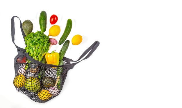 .shopping bag with assortment of fresh vegetables on white background