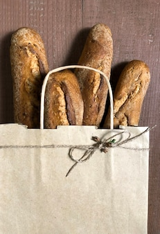 Shopping bag with bread on the wooden background, online delivery concept.