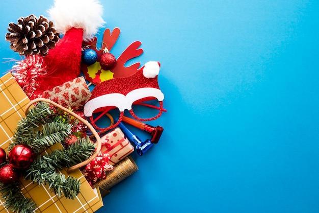 파란색 배경에 크리스마스 선물과 장식품이 있는 쇼핑백. 복사 공간