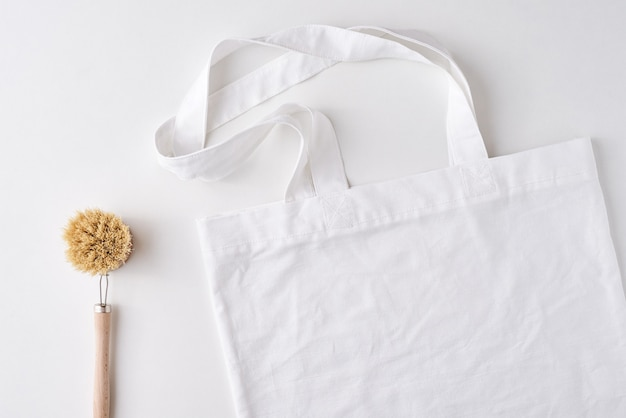 Shopping bag with copy space and wooden brush on a white background, top view.