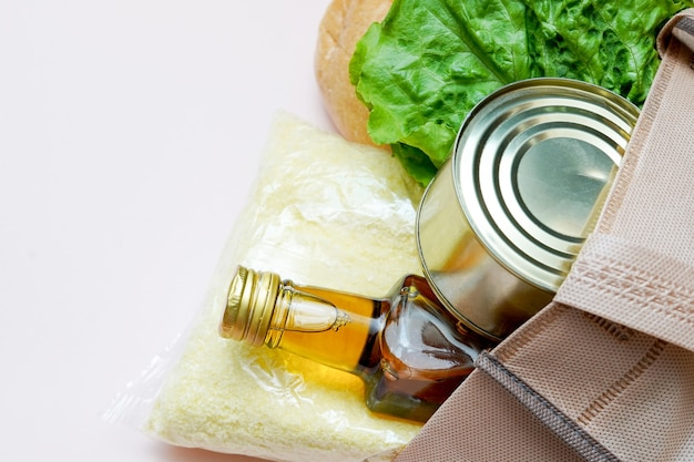 Shopping bag with food on light background, top view