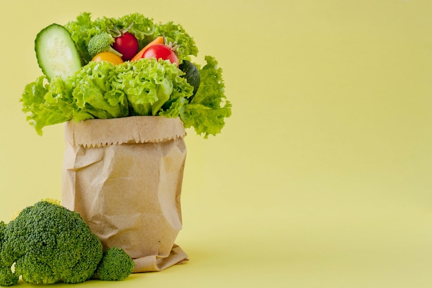 Shopping bag with groceries on yellow background