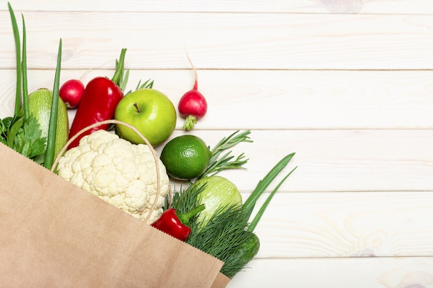 Shopping bag with healthy food on white background