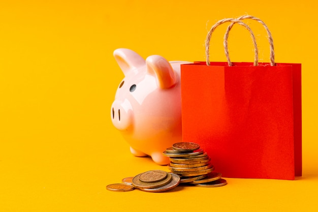 Shopping bag with stack of coins and piggy bank