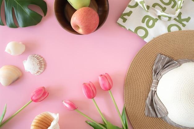 Сумки для покупок и аксессуары для летних каникул, фрукты и шляпа от солнца в розовом фоне