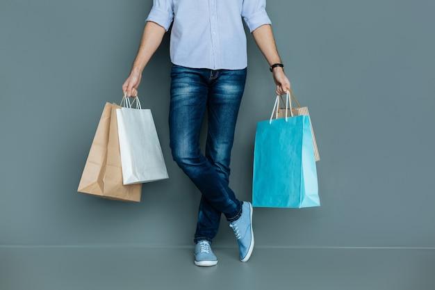 ショッピングバッグ。素敵なハンサムな若い男が持っているカラフルな買い物袋のクローズアップ