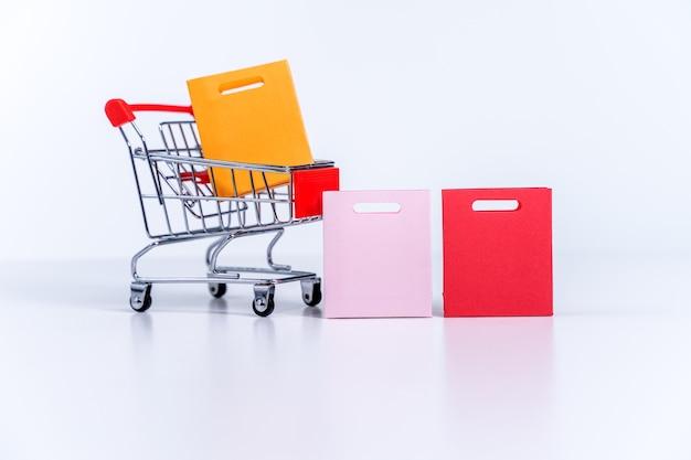 흰색 테이블 배경에 격리된 은색 쇼핑 카트에 든 쇼핑백, 집 주문 유지 개념, 닫기, 복사 공간 디자인.