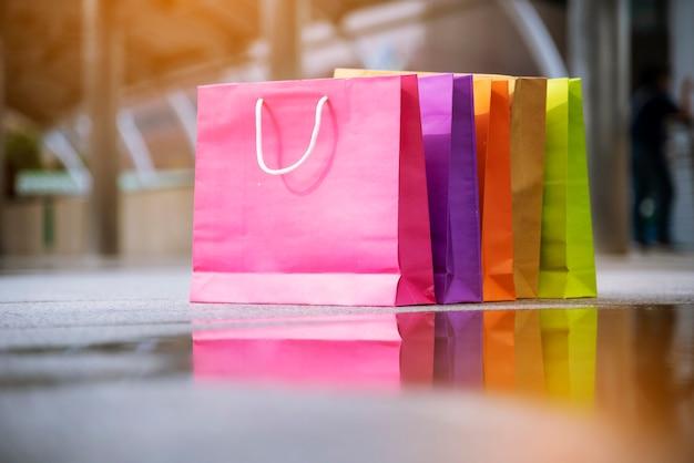屋内ショッピングモールで女性狂気の買い物中毒者の買い物袋