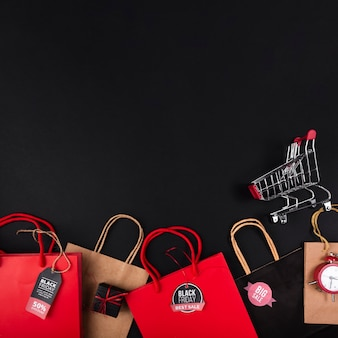 Shopping bags in various colors with shopping cart
