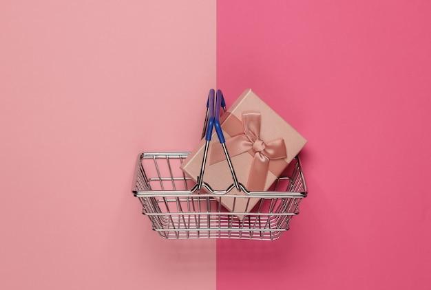 핑크 파스텔 바탕에 리본으로 쇼핑 바구니 및 선물 상자. 크리스마스, 생일 또는 결혼식을위한 구성. 평면도