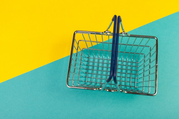 Shopping basket on a colored