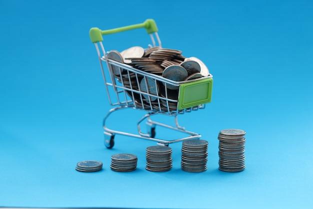 쇼핑 바구니에는 파란색 배경에 동전이 포함되어 있습니다. 컨셉 스토어에서의 통제되지 않은 지출