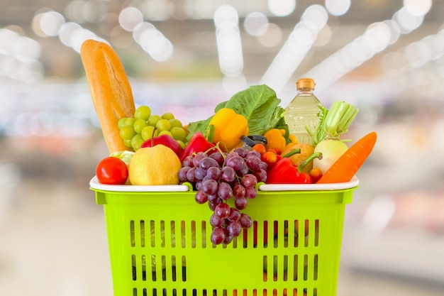 Shopping basket filled with fruits and vegetables with supermarket grocery store blurred defocused with bokeh light