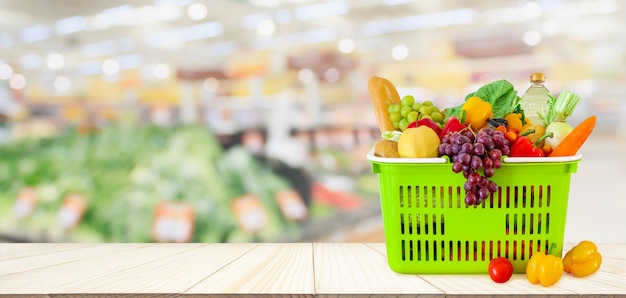 Shopping basket filled with fruits and vegetables on wood table with supermarket grocery store blurred defocused with bokeh light
