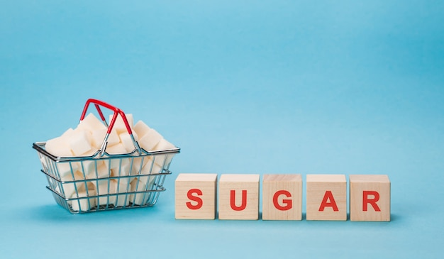A shopping basket full of cubes of white sugar. block letters of diabetes in a crossword puzzle.
