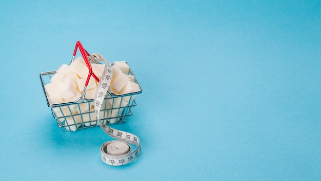 A shopping basket full of cubes of white sugar. a measuring tape is wrapped around the basket.