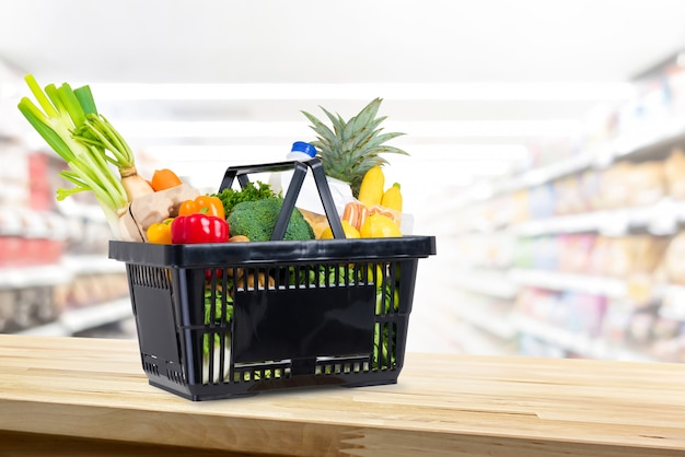 Shopping basket full of groceries on wood counter in supermarket background