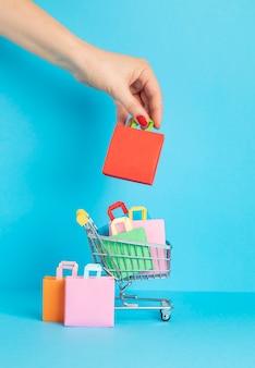 Корзина для покупок, полная бумажных пакетов. сезонная распродажа, онлайн-предложения, скидки, продвижение, концепция покупательской зависимости