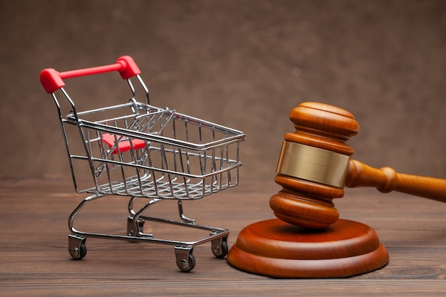 Shopping basket and judge gavel on wooden brown background.