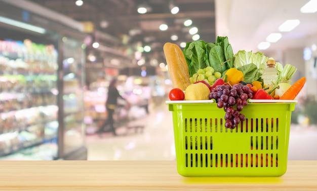 スーパーマーケットの背景を持つ木製のテーブルの上のショッピングバスケット