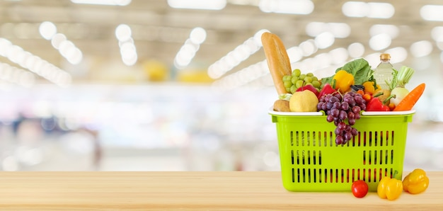 Корзина для покупок на деревянном столе с фоном супермаркета