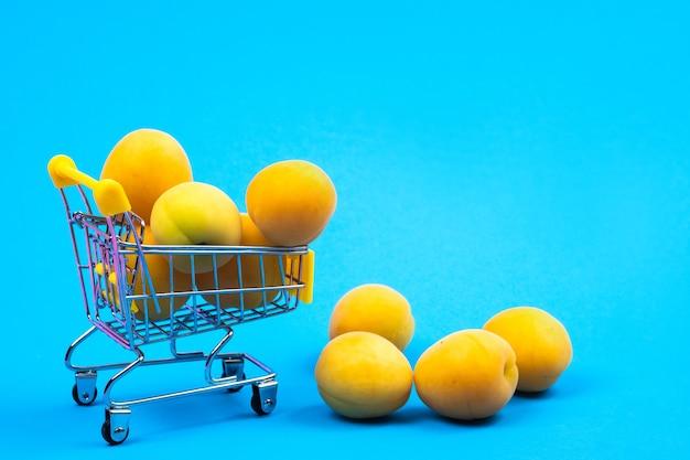 青い背景にアプリコットの買い物かご。ショッピングカート。