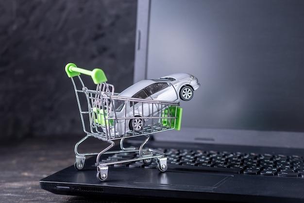暗い背景の上のラップトップキーボードの車とショッピングバスケット
