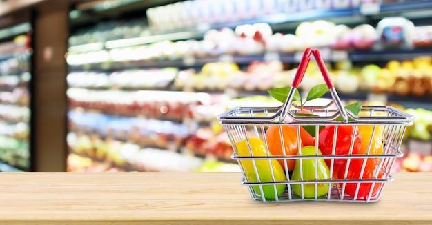식료품 점 슈퍼마켓 흐림 배경 위에 나무 테이블에 과일 쇼핑 바구니