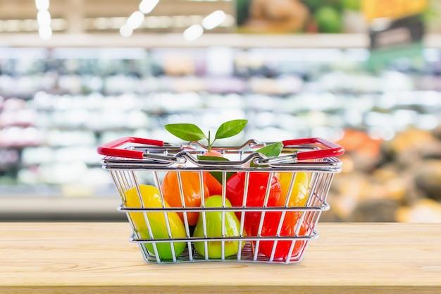 食料品店のスーパーマーケットの上の木製のテーブルに果物の買い物かごが背景をぼかす