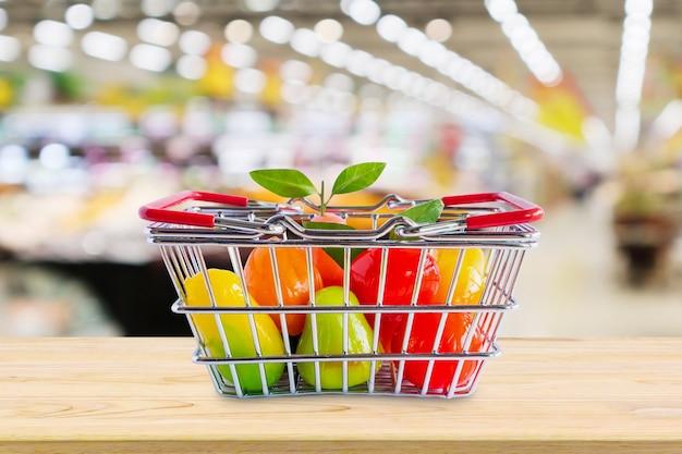 食料品店のスーパーマーケットで木のテーブルに果物と買い物かご